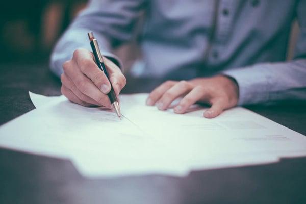 写真 人が紙にペンで何かを書いている、筆談の様子