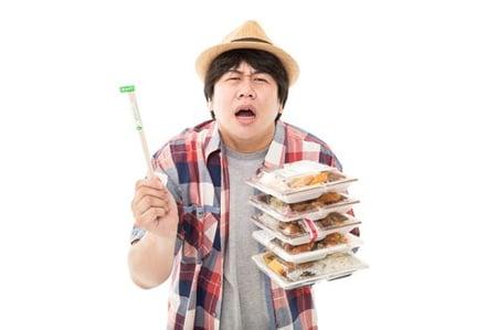 お弁当をいくつも持っている男性の写真